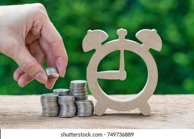 Woman hand holding stack of coins money putting on stack of coins and wooden alarm clock as long term investment time line or savings concept.