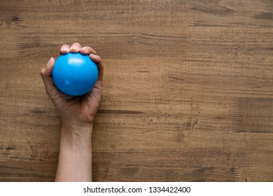 woman hand holding stress ball on wood table background