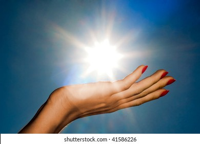 Woman hand holding the sun on a blue sky background