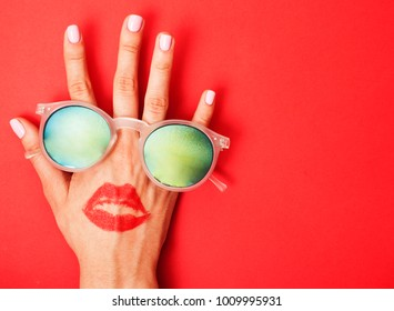 woman hand holding sunglasses on bright background, cosmetic summer vacation concept close up