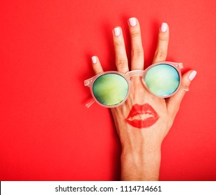 woman hand holding sunglasses on bright background, cosmetic sum