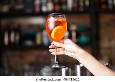 Woman hand holding tasty long drink in bar
