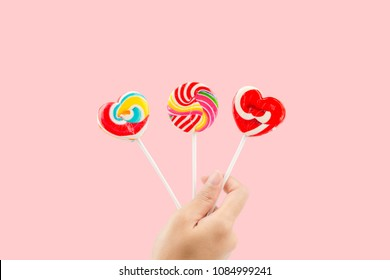 Woman hand holding three colorful lollipops isolated on pastel pink background with clipping path inside.