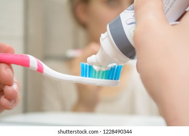 Woman hand holding a toothbrush with a toothpaste applied on it in the bathroom. Close up of female hand ready for brushing teeth. Young woman hand holding a pink toothbrush with white tooth paste.