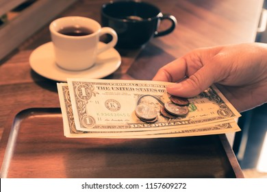 Woman hand holding US dollar banknotes and coins putting in wooden tray on cafe's table, two cups of tea on background, vintage style. Concepts for payment, service charge, bill checking, money tips.