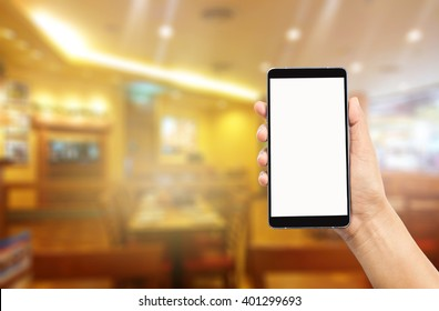 woman hand holding and using mobile over blurred image of restaurant background,Transactions by smart phone concept
