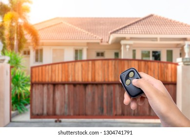 Woman hand holding and using remote control to open or close the automatic gate with modern home background. The auto door and Security system concept.