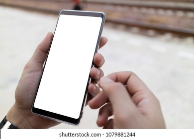 Woman hand holding and using smartphone with blank screen in park.Clipping path on screen.