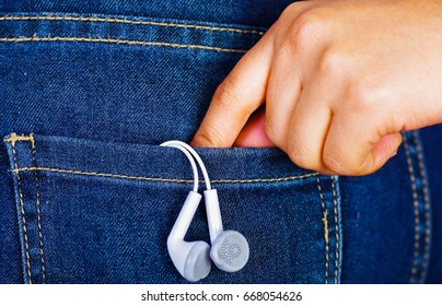 Woman hand holding a white headphones inside of jeans back pocket