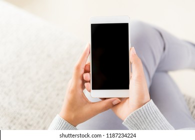 Woman hand holding white mobile phone and sitting on sofa at home.