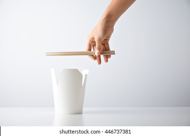 Woman hand holds chopsticks above opened blank takeway box with tasty noodles isolated on white Retail set presentation mockup