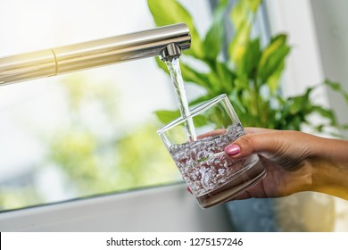 woman hand holds a glass to Filing it with water from tap