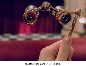 Woman hand holds opera binocular in theater against stage and drop-curtain
