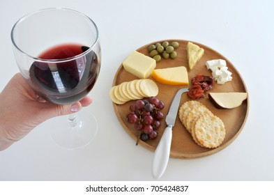 Woman hand holds a wineglass with red wine over a cheese platter. Food background. Copy space