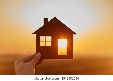 Woman hand holds wooden house against the sun. Solar energy. Children dreams. International day of families. Home protection insurance concept. Planning to buy property. A symbol for ecology.