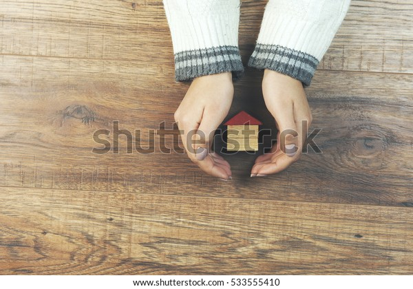 woman hand house model on wooden table