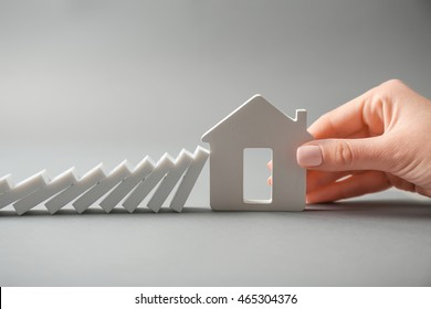 Woman hand with house shape and dominoes on grey background