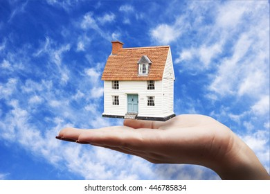 woman hand house in sky background