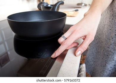 Woman hand includes modern induction stove