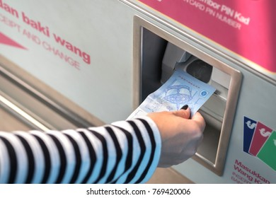 Woman hand inserts bank note for exchange monorail chip in machine