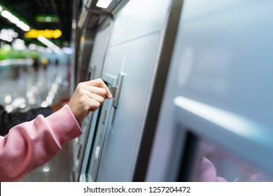 Woman hand inserts coin to buy subway train ticket in machine. Transportation concept