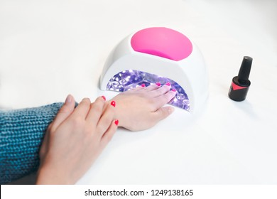 Woman hand inside UV lamp for nails on table close up. UV lamp for drying nails with gel method.