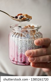 Woman hand keeps a jar of glass full of chia pudding and metal spoon full of pudding, oatmeal flakes and black currant above the jar