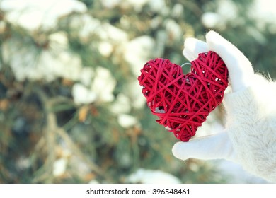 Woman hand in knitted mitten holding red heart on winter background