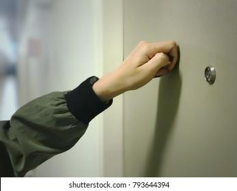 Woman hand is knocking the door.
