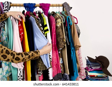 Woman hand looking through her wardrobe with colorful clothes and accessories. Full rack of clothes on hangers and a pile of clothes on the shelf, unrecognizable woman searching for clothes.
