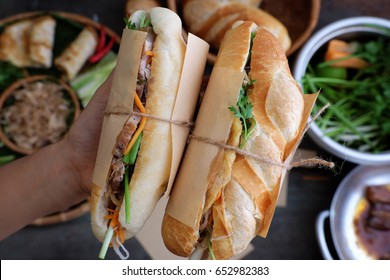 Woman hand make banh mi thit or Vietnamese bread, famous street food from  raw material: pork, ham, pate, egg and fresh herbs as scallions, coriander, carrot, cucumber, chilli.