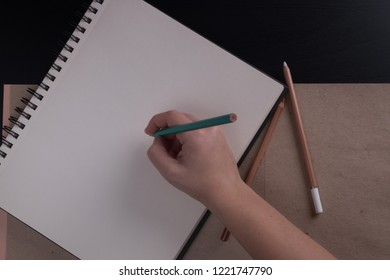 Woman hand making notes in notebook. Sketchbook with pencils on a dark background. Female hand draws in the sketchbook.