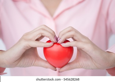 Woman hand making sign as heart while holding red heart ball for love