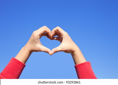 Woman hand making sign Heart in red cloth over the sky