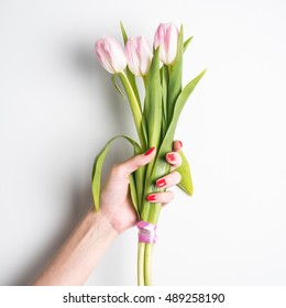 Woman hand with manicure holding tulips flowers on white background