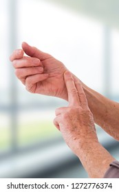 Woman hand measuring her own arm pulse