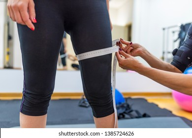Woman hand measuring leg with white measuring tape, reducing excess weight. Healthcare and sport concept. Time for diet slimming weight loss. Fitness woman girl in sportswear with measure tape