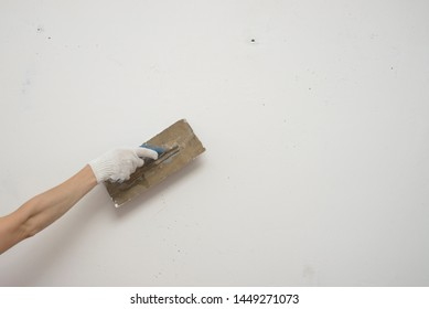 woman hand with metal big spatula, to equalize the plaster filler on the wall. Putty walls with their own hands.
