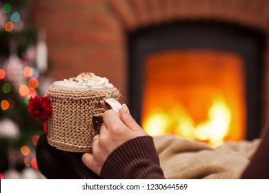 Woman hand on armchair with a cup of hot chocolate resting in front of fireplace and christmas tree - closeup