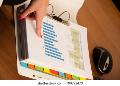 Woman hand on a front page of a business folder checking data