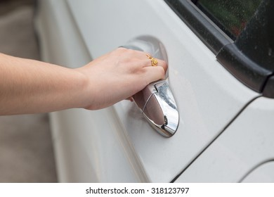 Woman hand open white car door with emty space