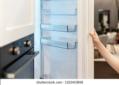 Woman hand opening white modern built-in freezer with empty shelf