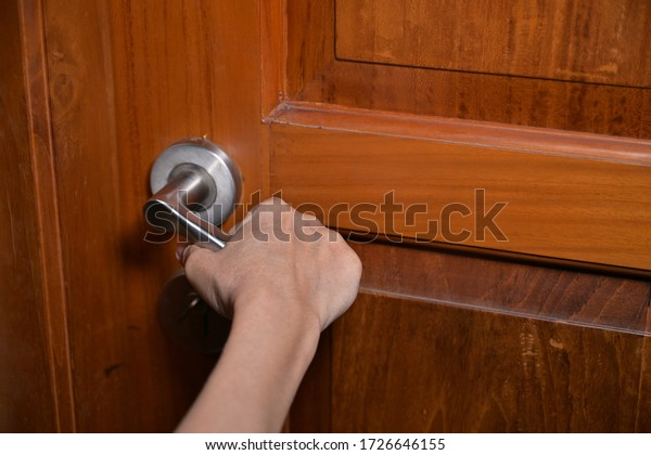 Woman hand opening wooden door close up view