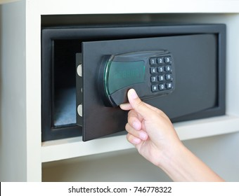 Woman hand opens a safe hidden in the wardrobe at the hotel.