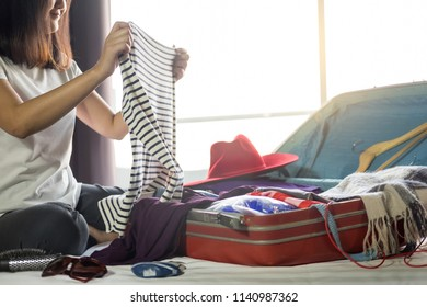 Woman hand packing a luggage for a new journey and travel for a long weekend