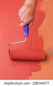 Woman hand painting a floor on color red for waterproofing. She is using a paint roller.