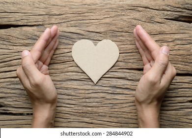 woman hand with paper heart on wood background