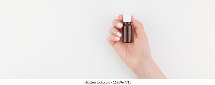Woman hand with pastel manicure polish holding small glass bottle long wide banner background copy space. Mock up for natural oil spa treatment, medical products. Female healthcare wellness concept