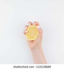 Woman hand with pastel manicure polish holding a half of lemon isolated on white background copy space minimalism style. Square Template for feminine social media. Healthy eating concept