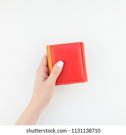 Woman hand with pastel manicure polish holding bright red leather wallet isolated on white background with copy space minimalism style. Square Template for feminine beauty blog social financial media